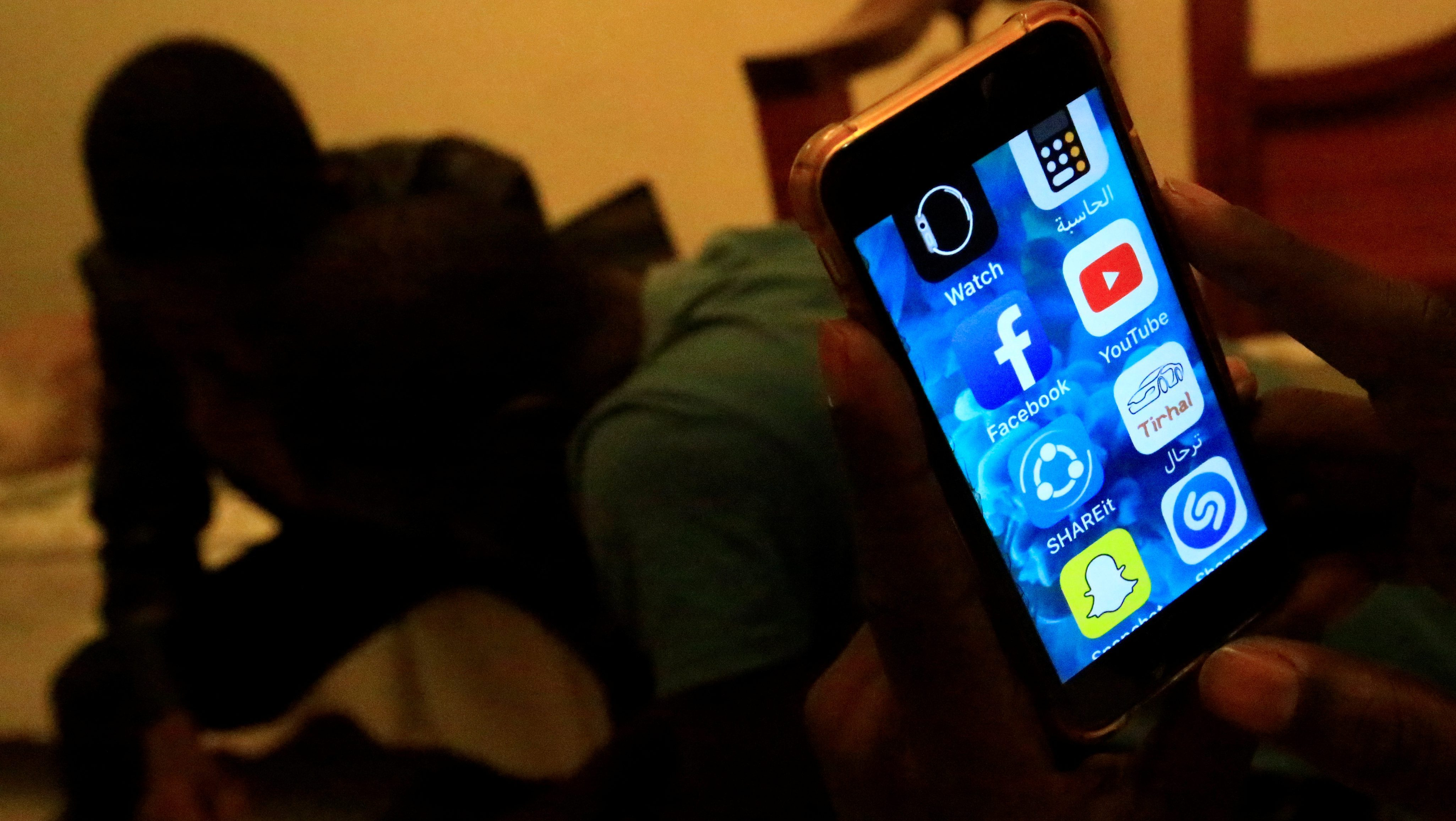 A Sudanese man holds his phone with restricted internet access social media platforms, in Khartoum