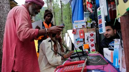 Hindu pilgrims make calls at a stall run by a Kashmiri Muslim before their journey towards the holy cave of Amarnath, at a base camp near Pahalgam