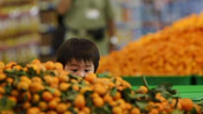 A child eyes oranges at a Hypermart supermarket in Jakarta