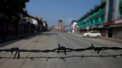 Barbed wire is seen laid on a deserted road during restrictions in Srinagar