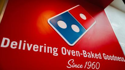 """A sign at a Domino's Pizza that reads """"Delivering oven-naked goodness since 1960"""" with the Domino's domino-piece logo."""