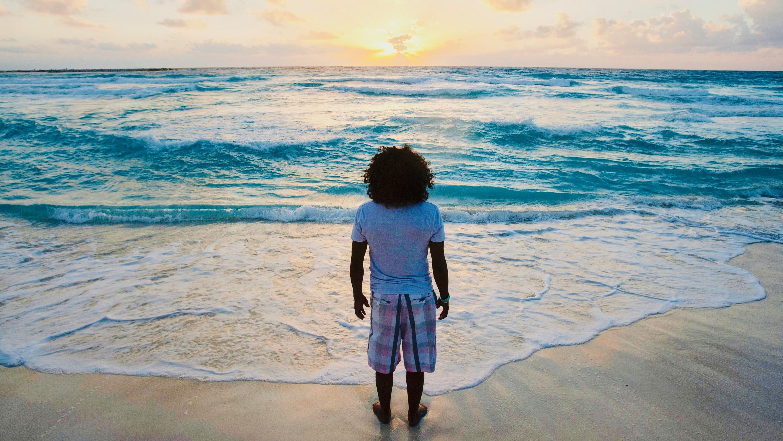 A man watches the sunrise on New Year's Day at Gaviota Azul beach in Cancun.