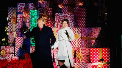 Donald and Melania Trump in front of a stack of wrapped packages at a White House Christmas ceremony outdoors.