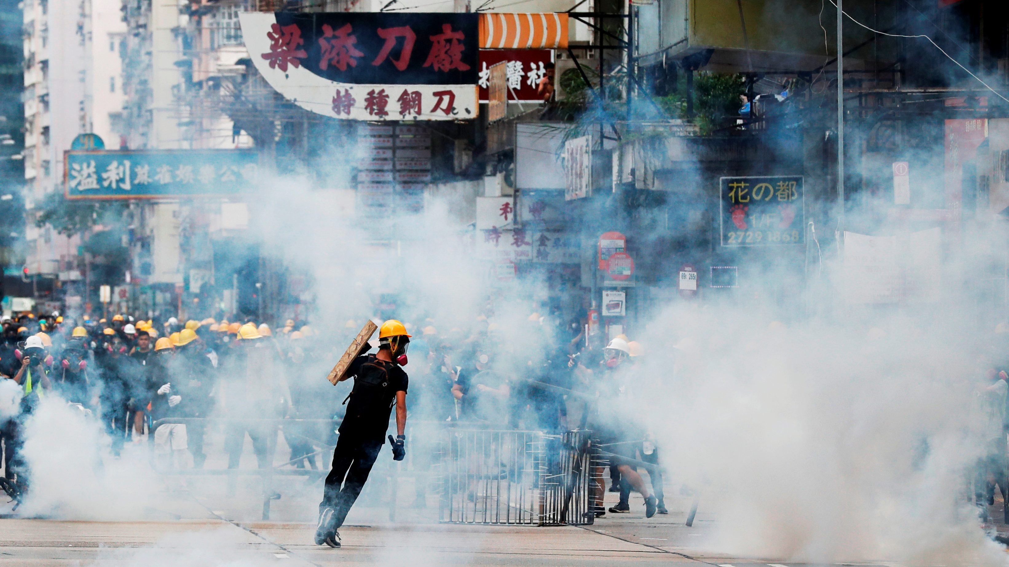 Anti-extradition bill protesters react from tear gas as riot police try to disperse them during a protest at Sham Shui Po in Hong Kong