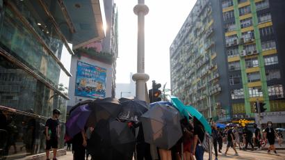 Protesters use umbrellas to shield themselves as people damage smart lamppost in Ngau Tau Kok in Hong Kong.