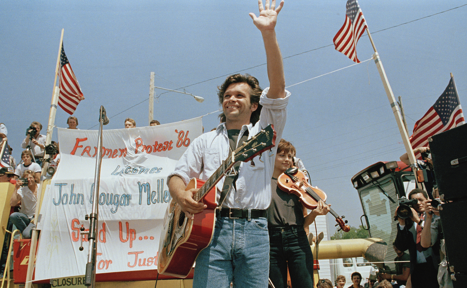 Singer John Cougar Mellencamp waves to the crowd in Chillicothe, Mo., as he arrives on stage to perform at the farmer's rally, May 7, 1986. The three-song concert was held in the parking lot of the Livingston County, Mo., FmHA office. Local farmers have occupied that site since March 17 to protest the policies of the county FmHA supervisor. (AP Photo)