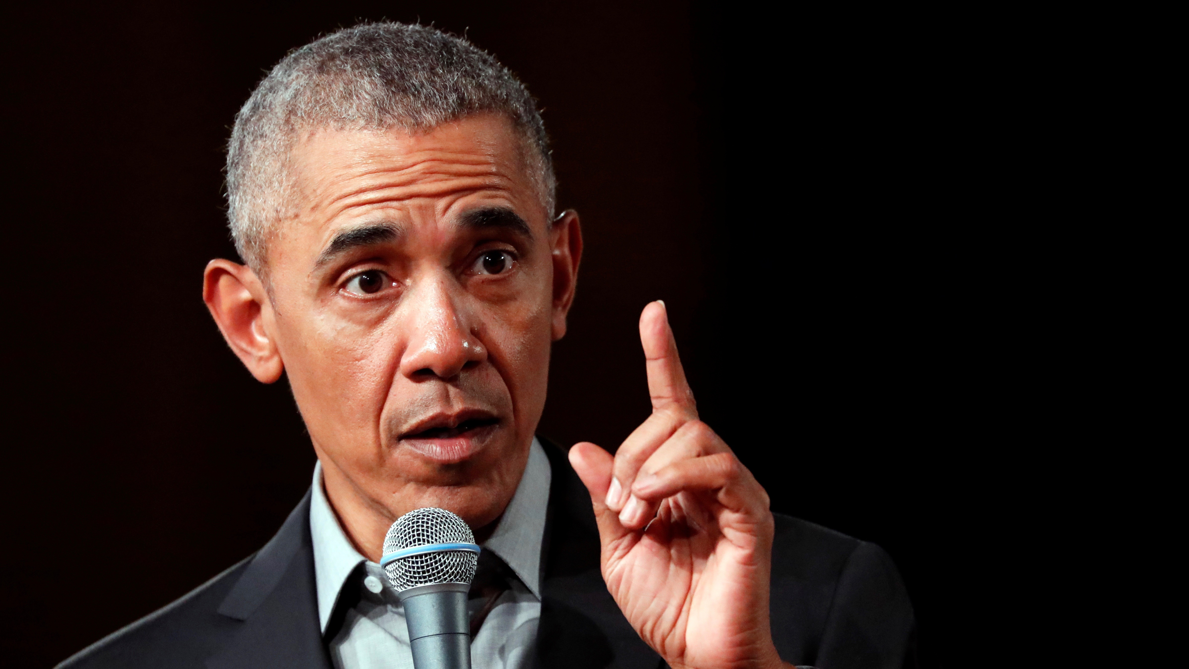 Image of Barack Obama in 2019 with his finger pointing up and microphone in one hand.