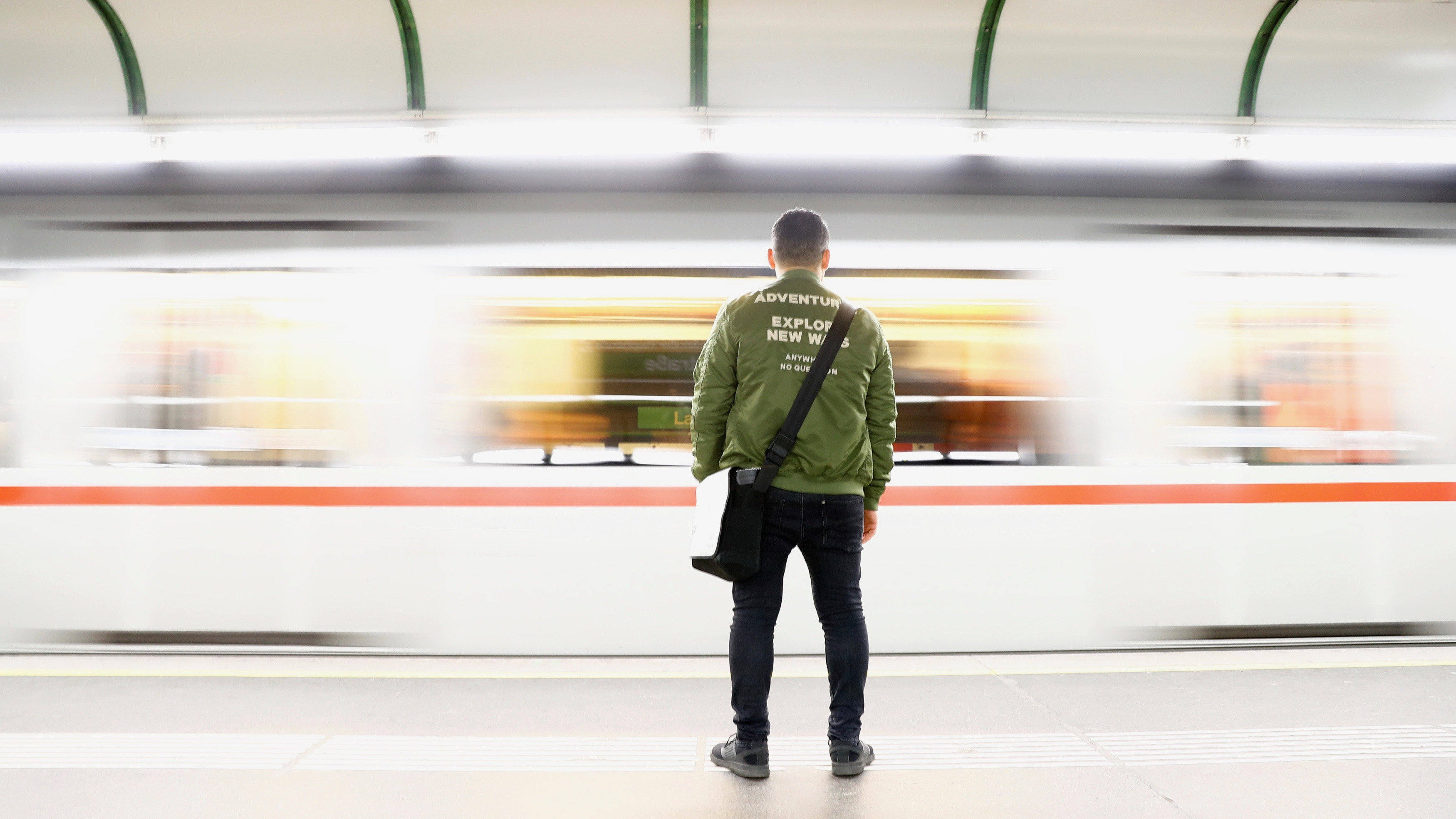 A man waits on platform as subway rushes by in Vienna.