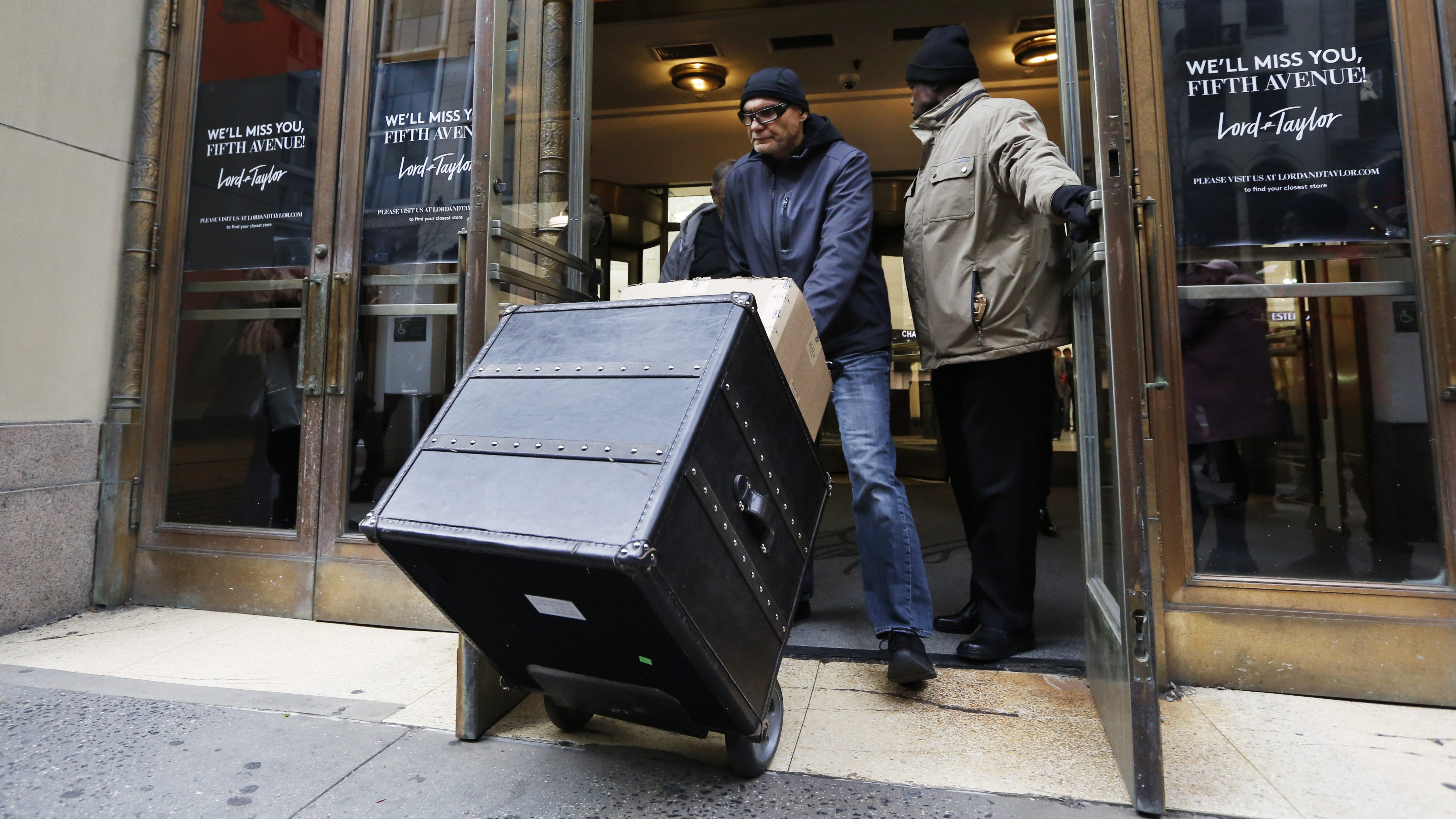 A man wheels a case out of the WeWork-owned Lord and Taylor building.