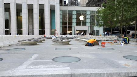 Workers cementing metallic objects onto the ground outside the new Apple Store