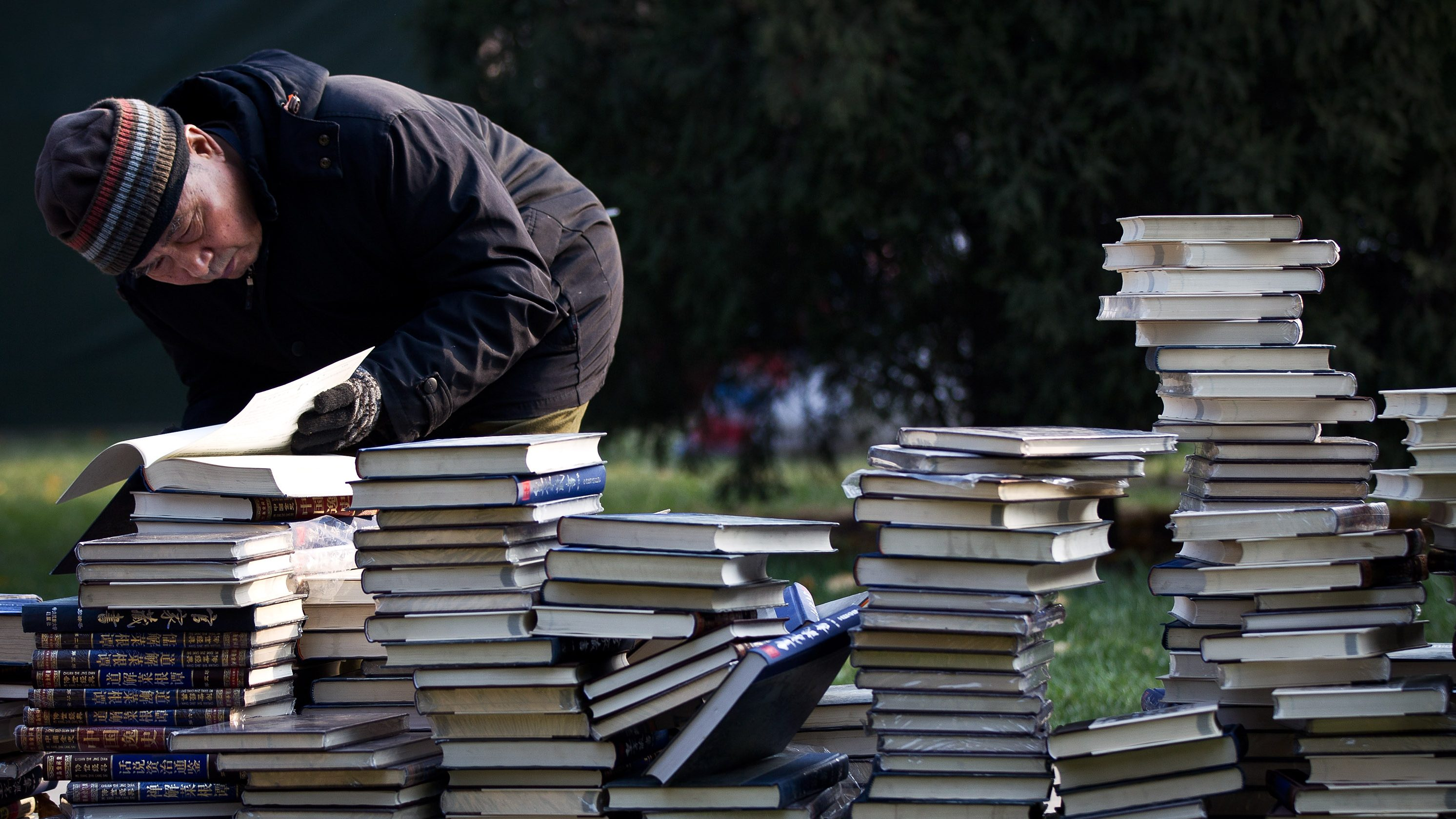 An elderly man browses one of books piled up on the grass for sale during the Winter Book Fair held at Ditan Park in Beijing, Sunday, Nov. 27, 2011.