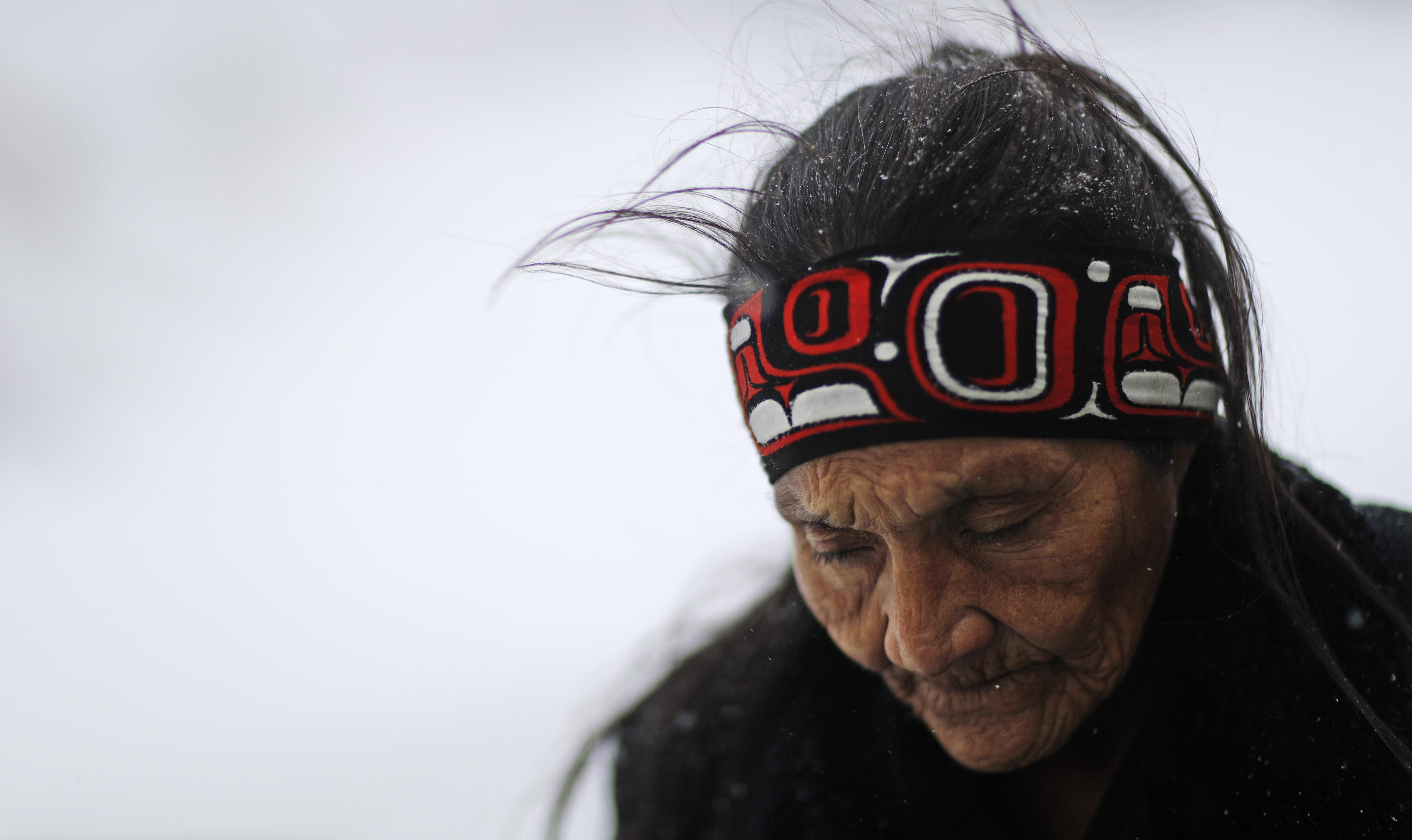 In this Tuesday, Nov. 29, 2016 photo, Grandma Redfeather of the Sioux Native American tribe walks in the snow to get water at the Oceti Sakowin camp where people have gathered to protest the Dakota Access oil pipeline in Cannon Ball, N.D.