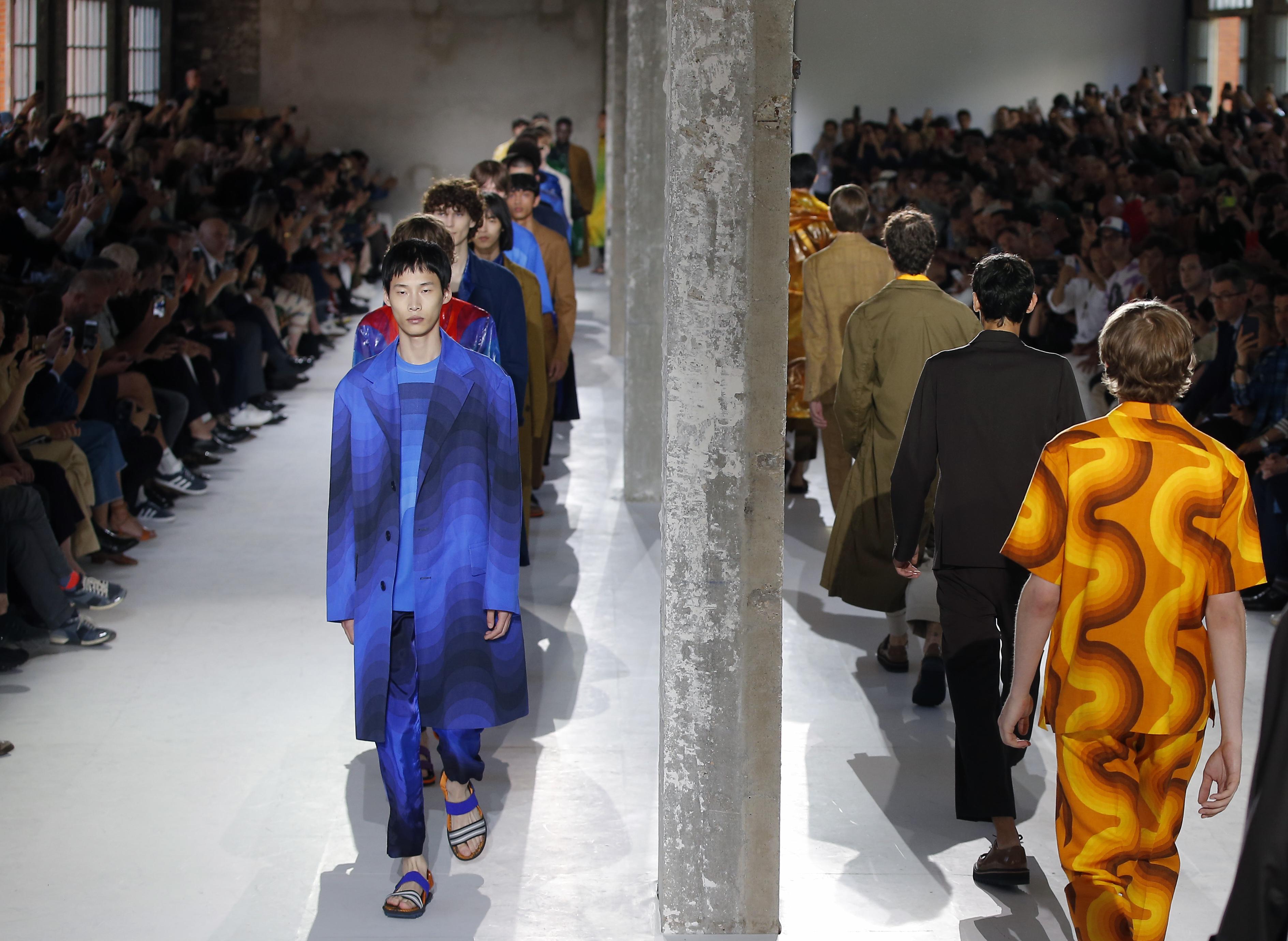 Men in bright undulating prints walk the runway