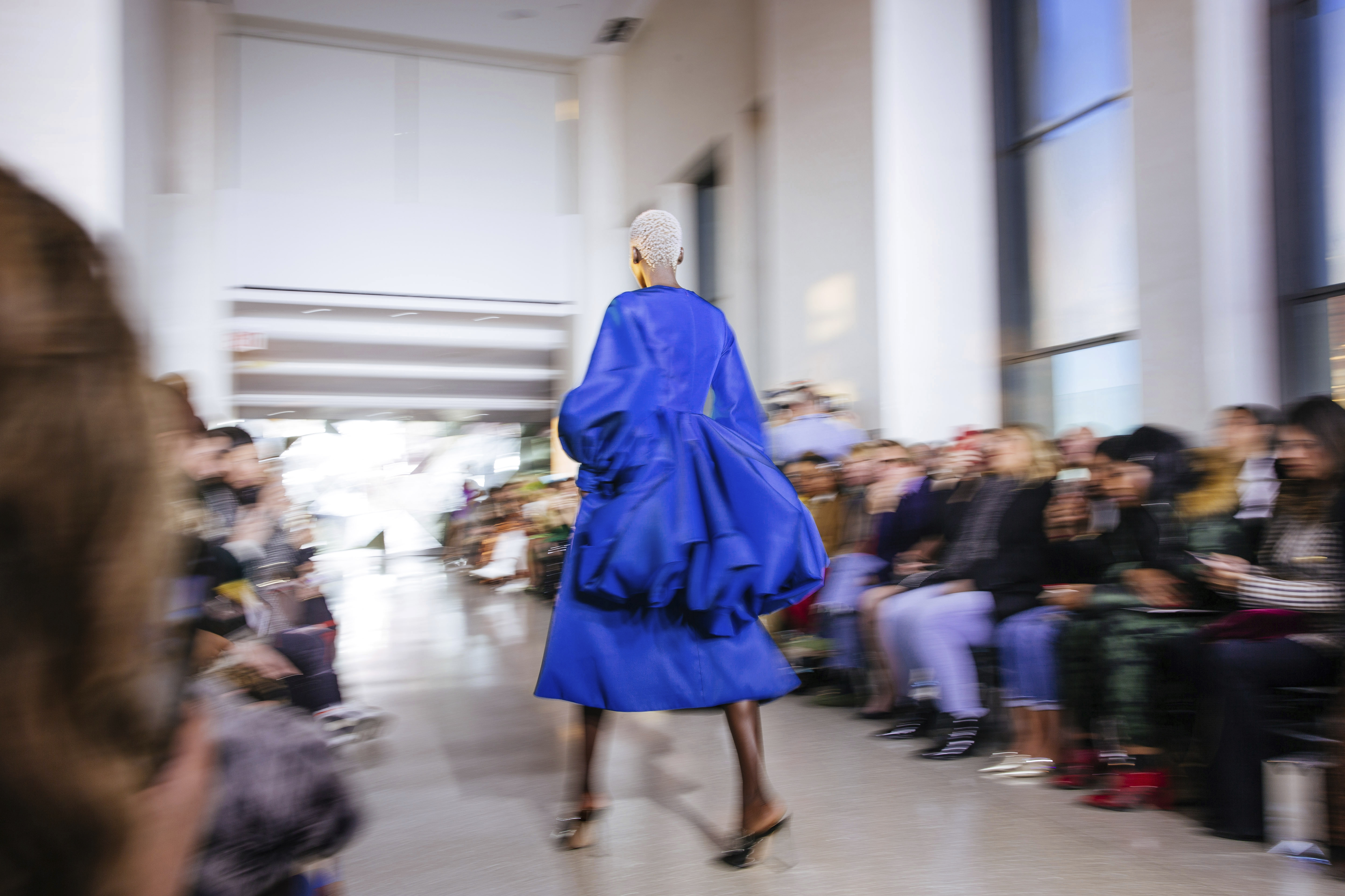 A bright blue dress stands in focus on the runway