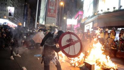 A protester with a shield run past fires in Causeway Bay