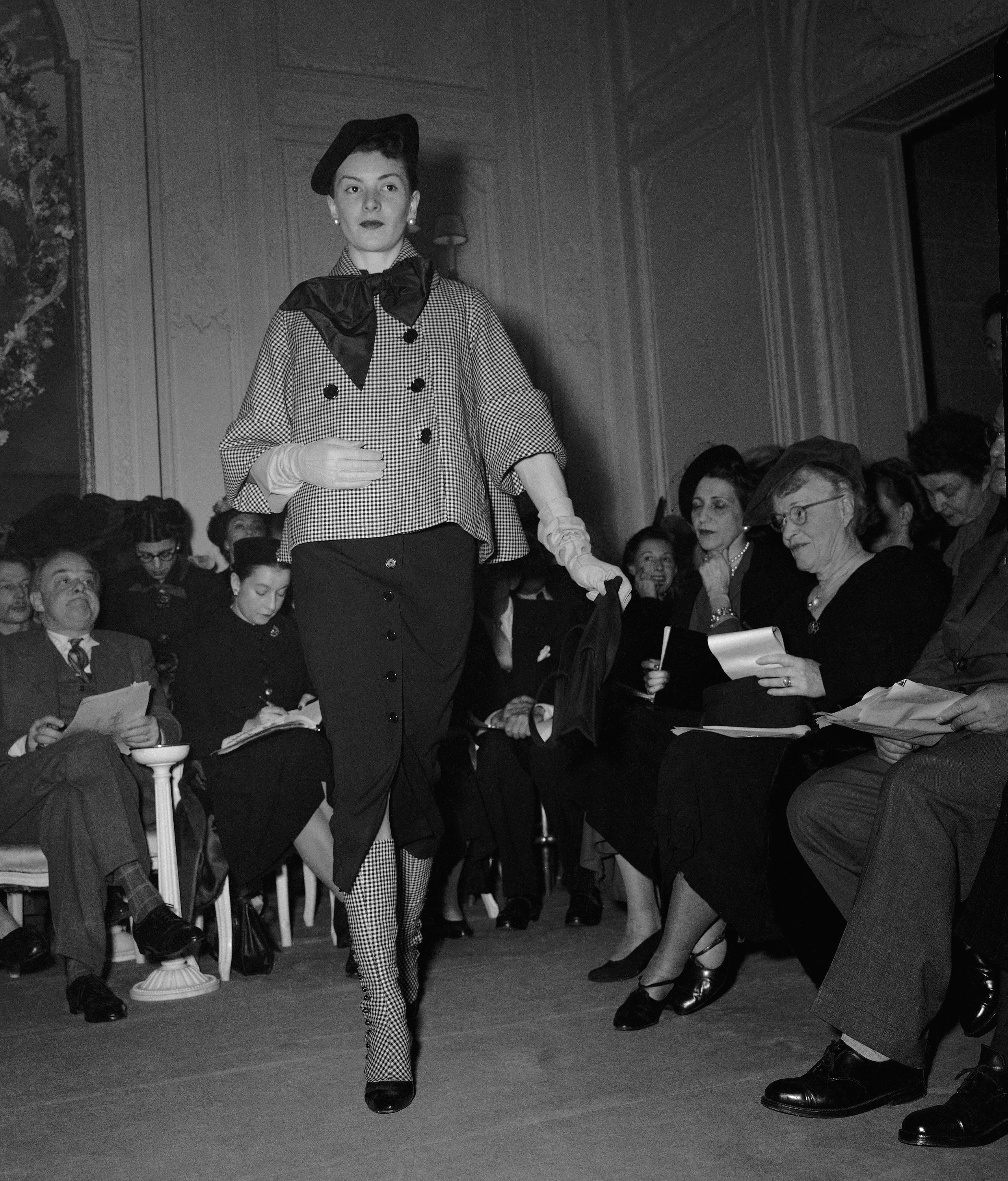 A woman walks in a black and white checkered, flamed jacket with matching gaiters. Under the jacket is a black wool dress, its narrow skirt shorter than those in many collections of the time and split in front. A black satin bow and a black beret complete the ensemble.