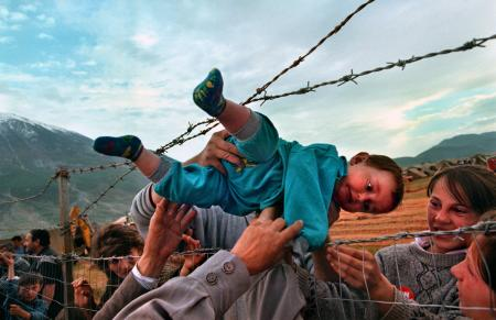 Agim Shala, 2 years old, is passed thru the barbed wire fence at a refugee camp as members of the Shala family are reunited after fleeing Kosovo, in 1989. The relatives who just arrived from Prizren had to stay outside the camp until shelter was available.