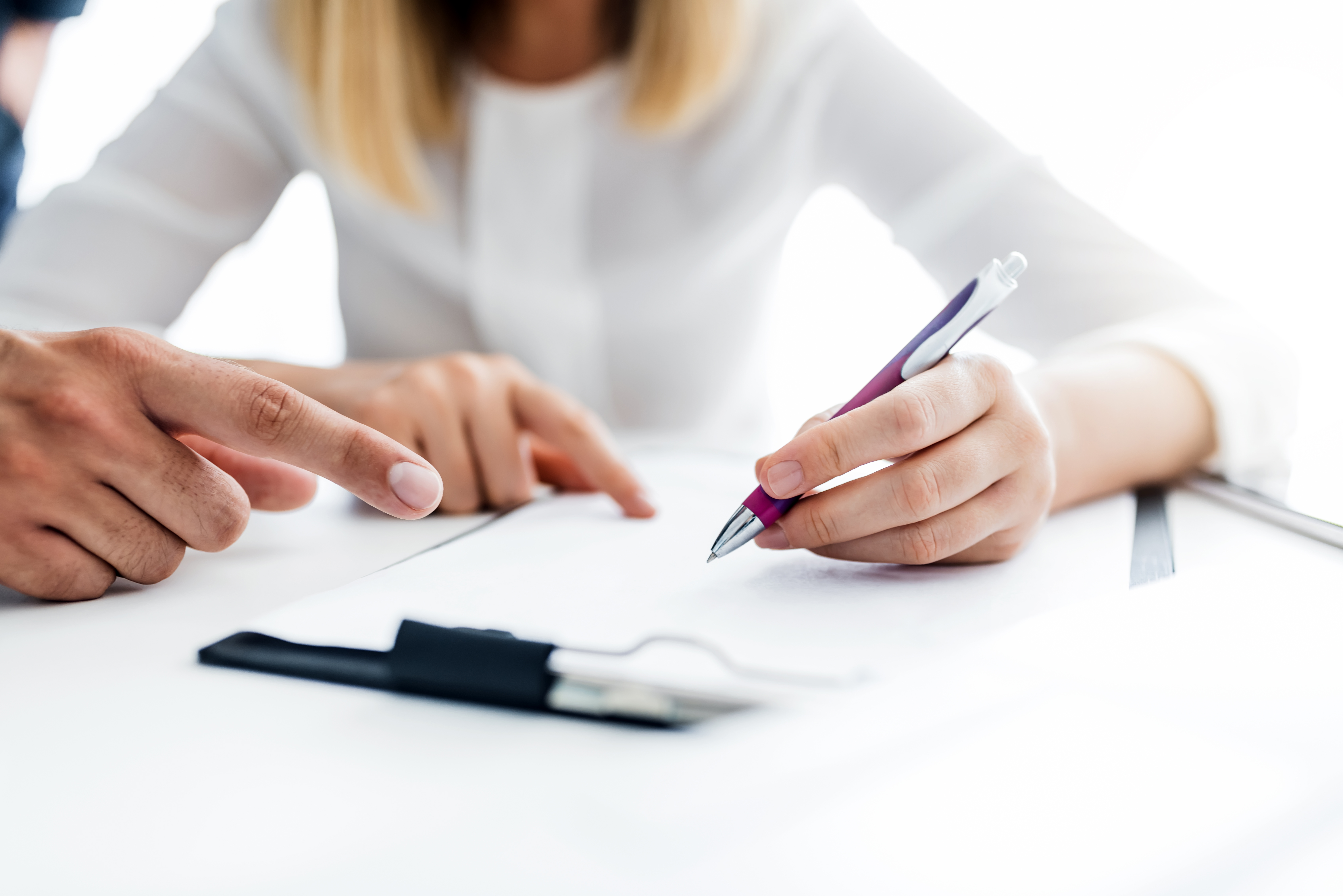 Photo of woman signing document