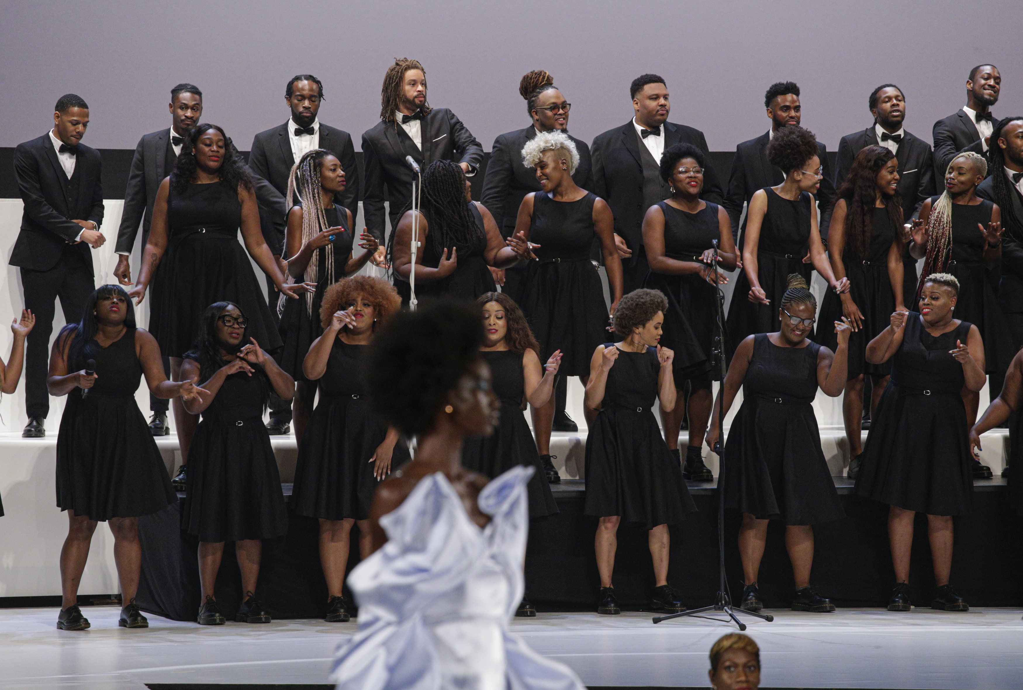 A choir of women in black dresses and men in black tuxes sing and dance during the Pyer Moss show