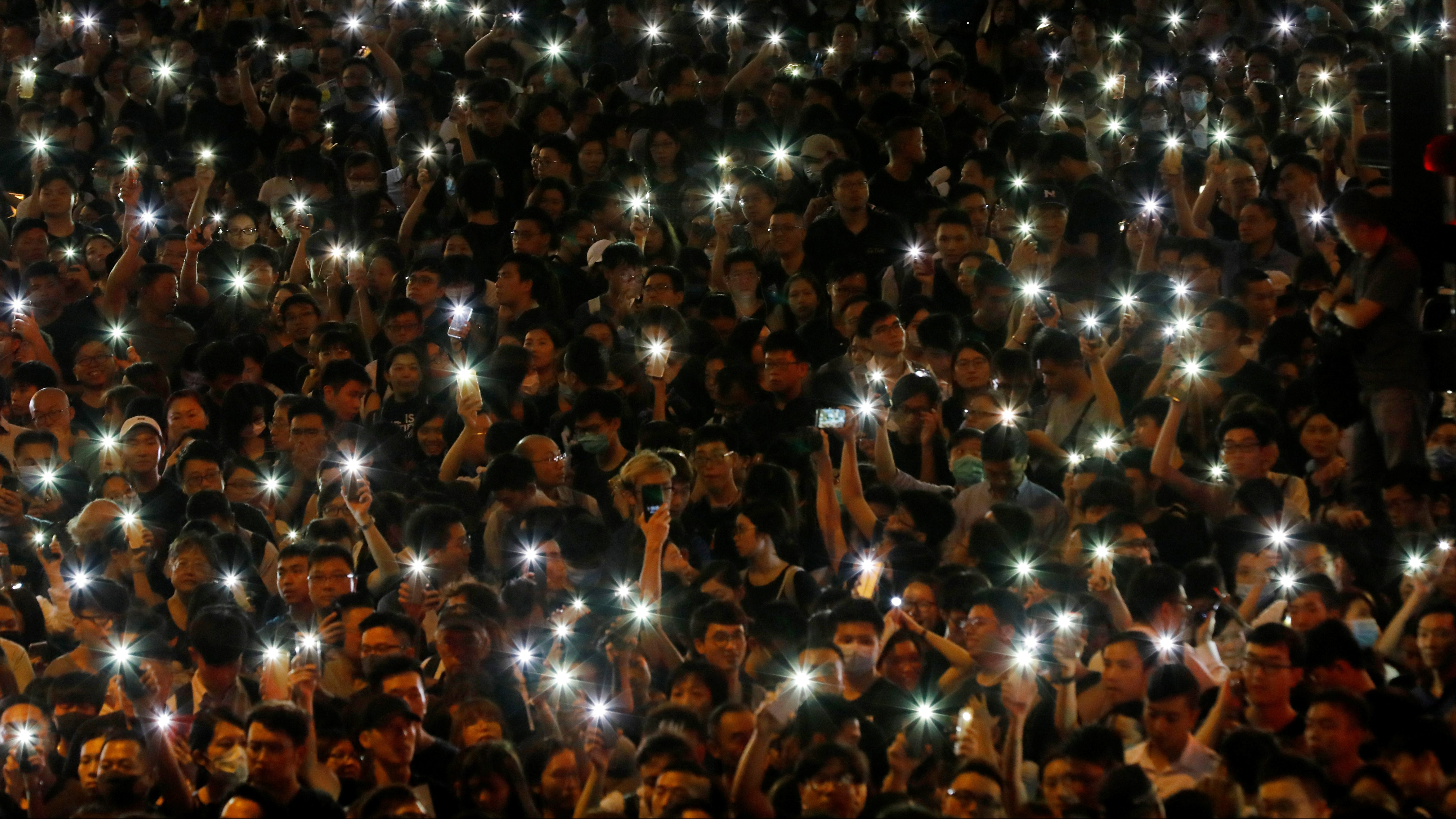 Attendees hold up their lit mobile phones during a rally by civil servants to support the anti-extradition bill protest in Hong Kong, China.