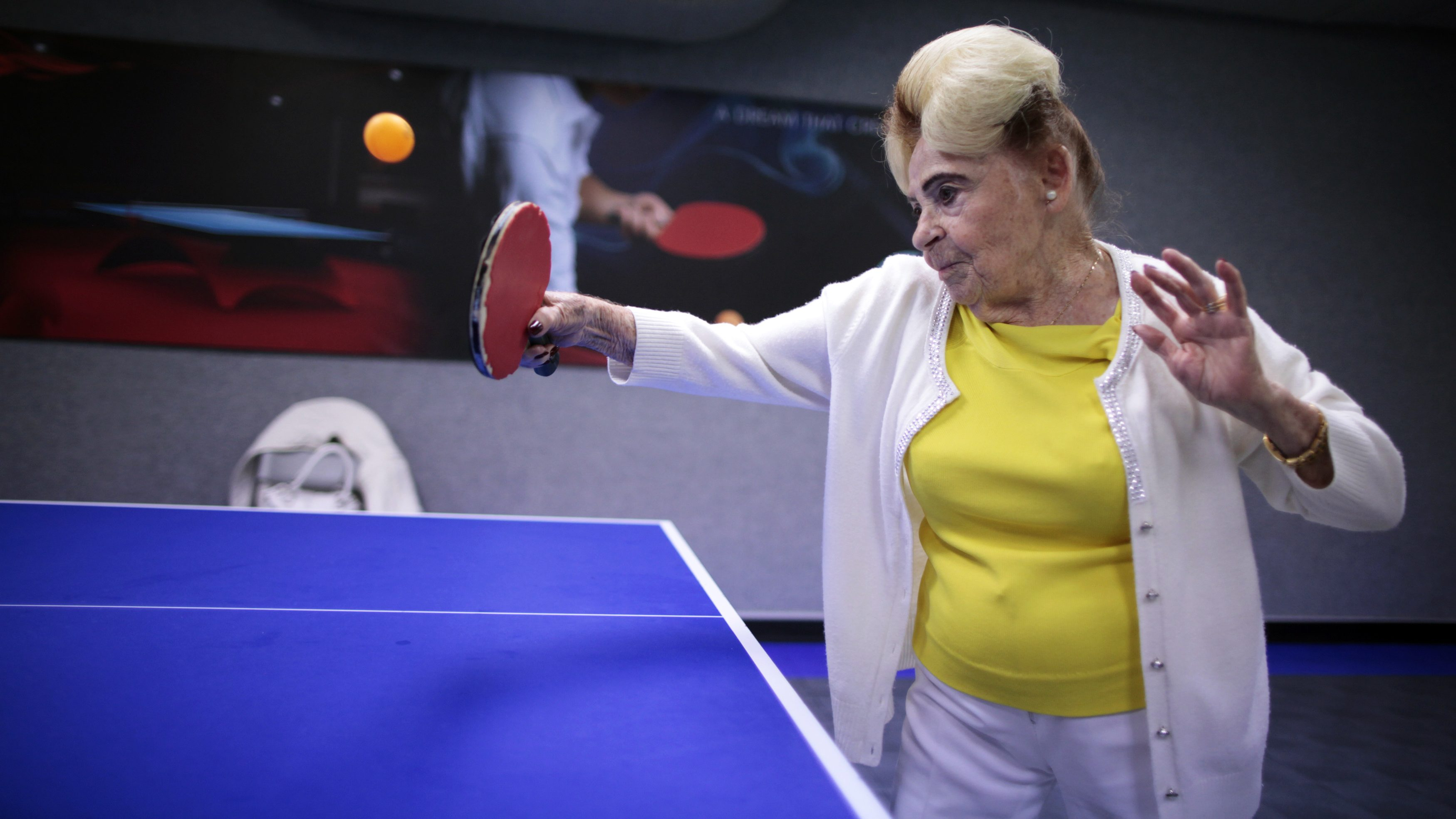 An elderly woman plays pingpong