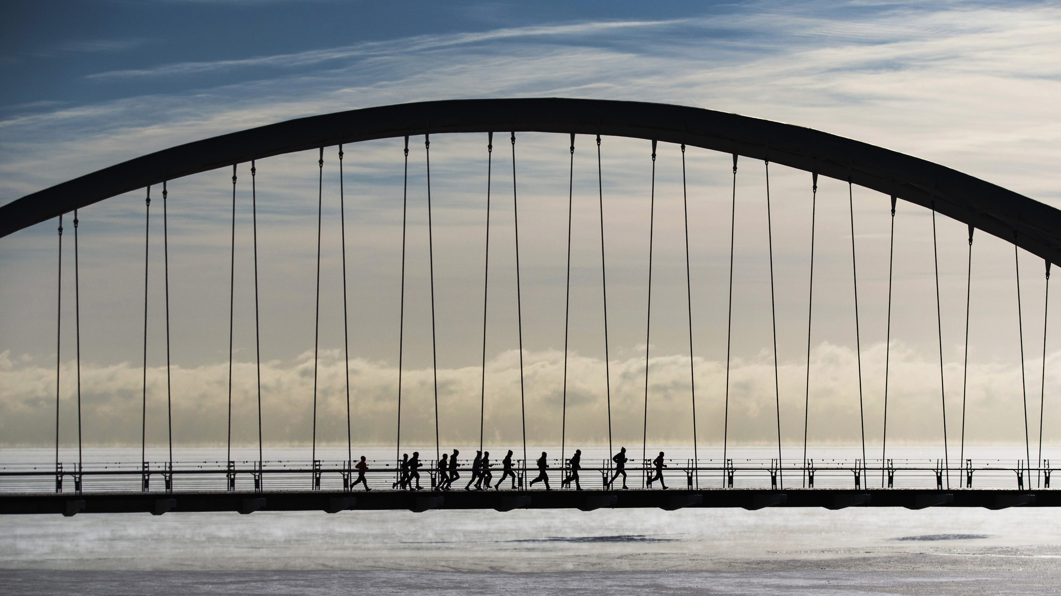 Group of joggers run across the Humber Bay Arch Bridge during extreme cold temperatures in Toronto