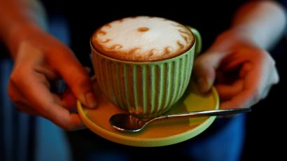A barista holds a cappuccino coffee at the La Tercera cafe in Beijing