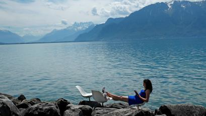 Woman reads a book on a warm spring day on the shore of Lake Leman in Vevey