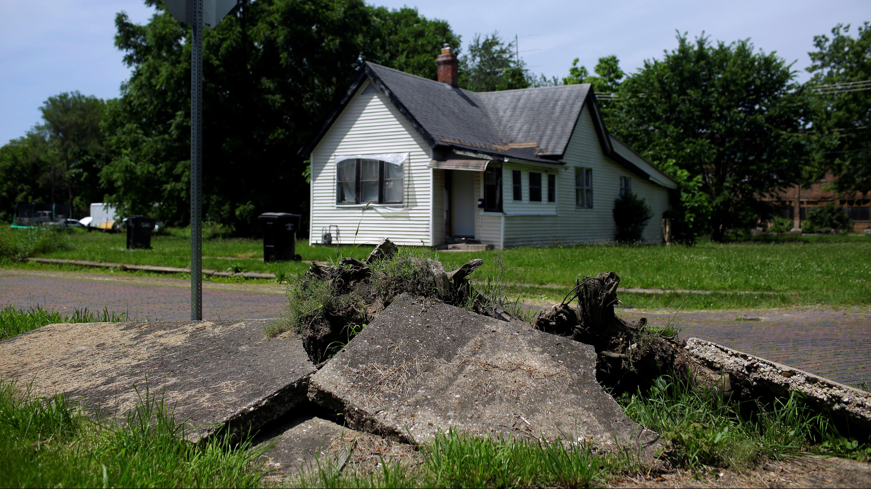A house behind a buckled sidewalk.