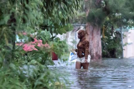 A woman walks in a flooded street in Nassau on Sept. 2.