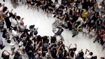 A man holds up a tuba as protesters shout slogans and sing Hong Kong's anthem during a protest at New Town Plaza shopping mall in Hong Kong, China September 11, 2019.