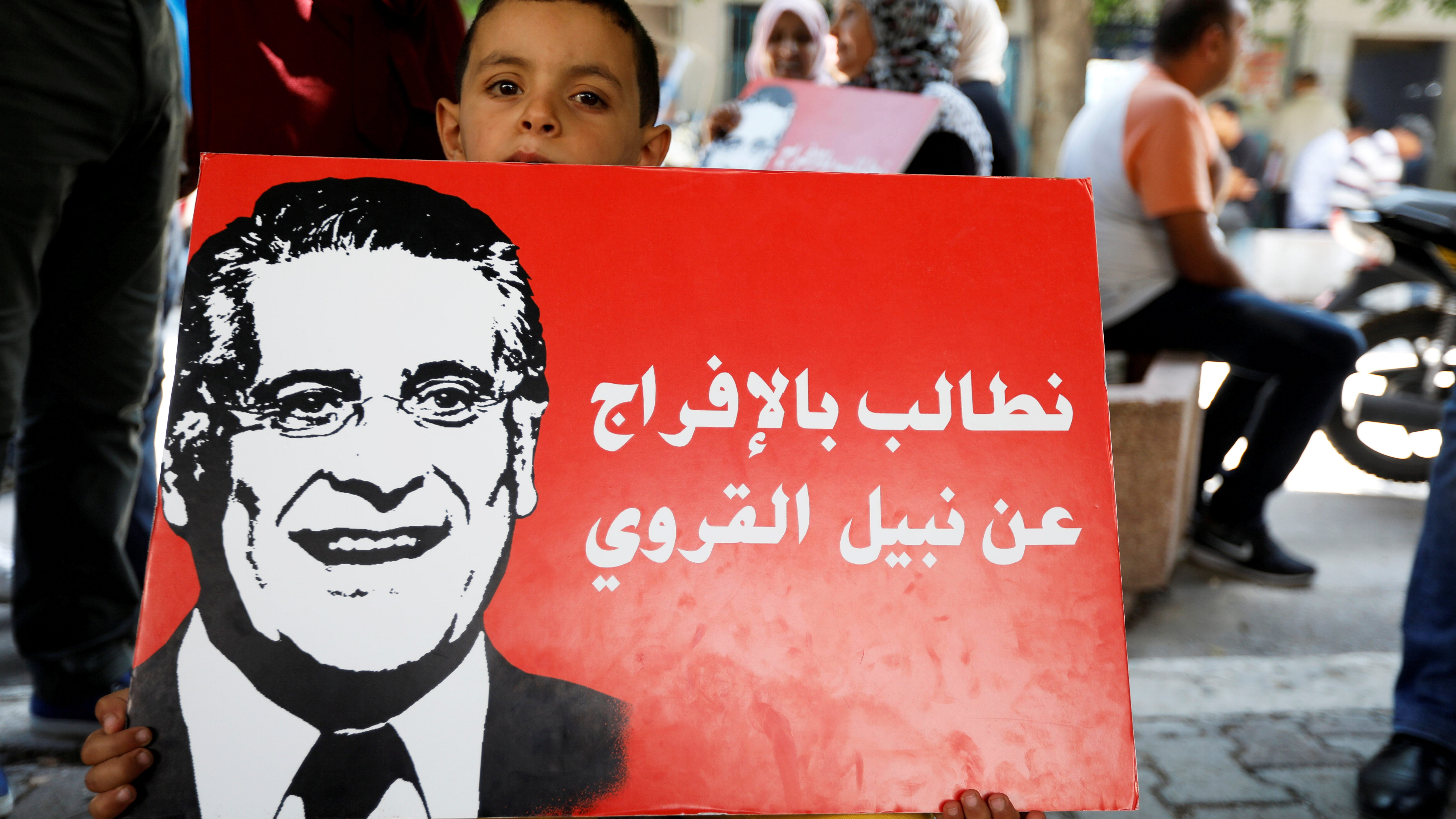"A boy holds a picture of presidential candidate Nabil Karoui as he takes part in a rally asking for his release from prison, in front of the courthouse in Tunis, Tunisia, September 3, 2019. The placard reads ""Release Nabil Karoui"" ."