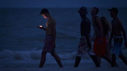 A person looking at their cell phone while they walk on the twilight beach.