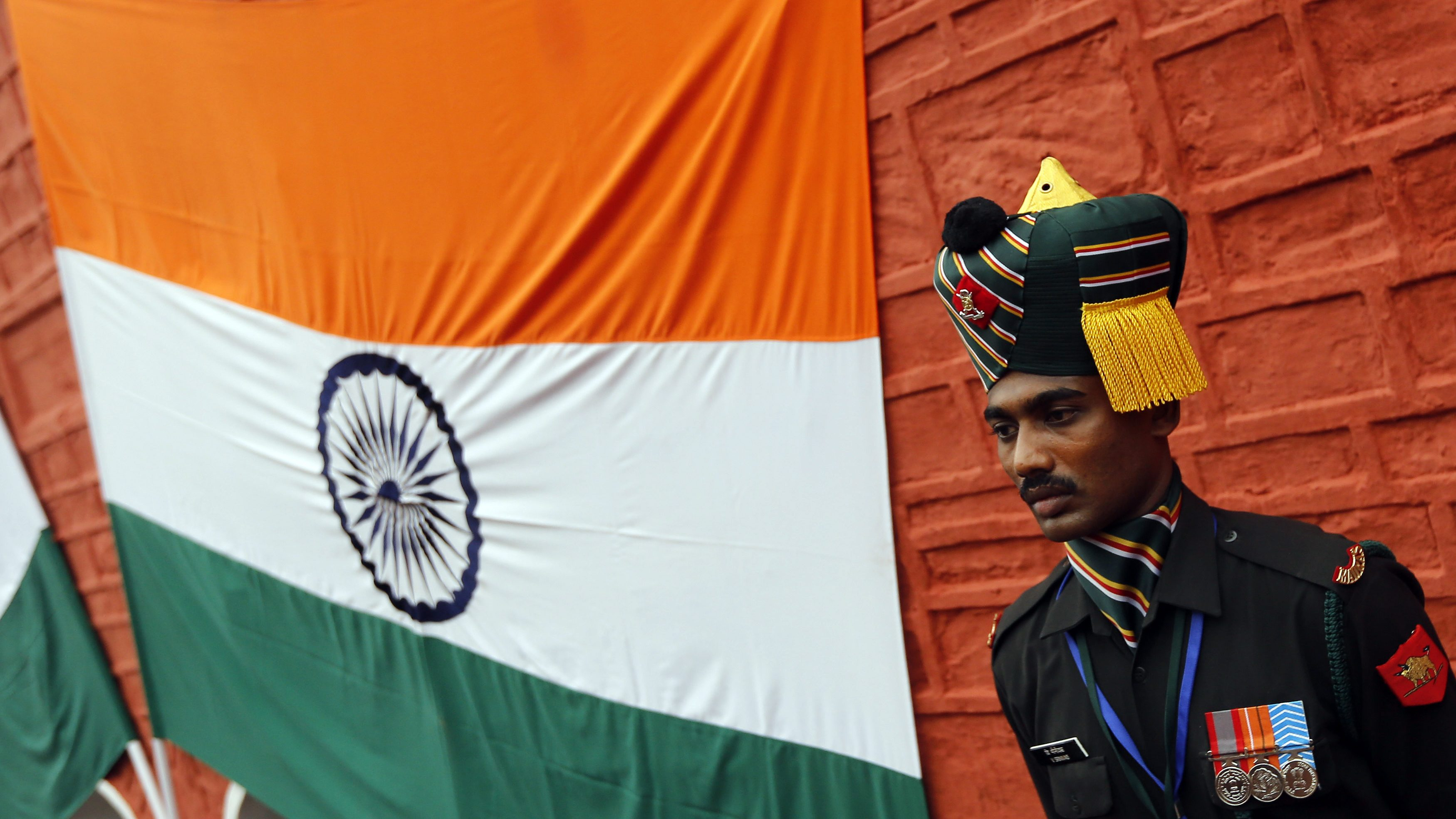 An Indian soldier stands next to an Indian national flag during the full-dress rehearsal for India's Independence Day celebrations at the historic Red Fort in Delhi August 13, 2013. India commemorates its Independence Day on August 15. REUTERS/Adnan Abidi (INDIA - Tags: ANNIVERSARY MILITARY) - GM1E98D136Y01