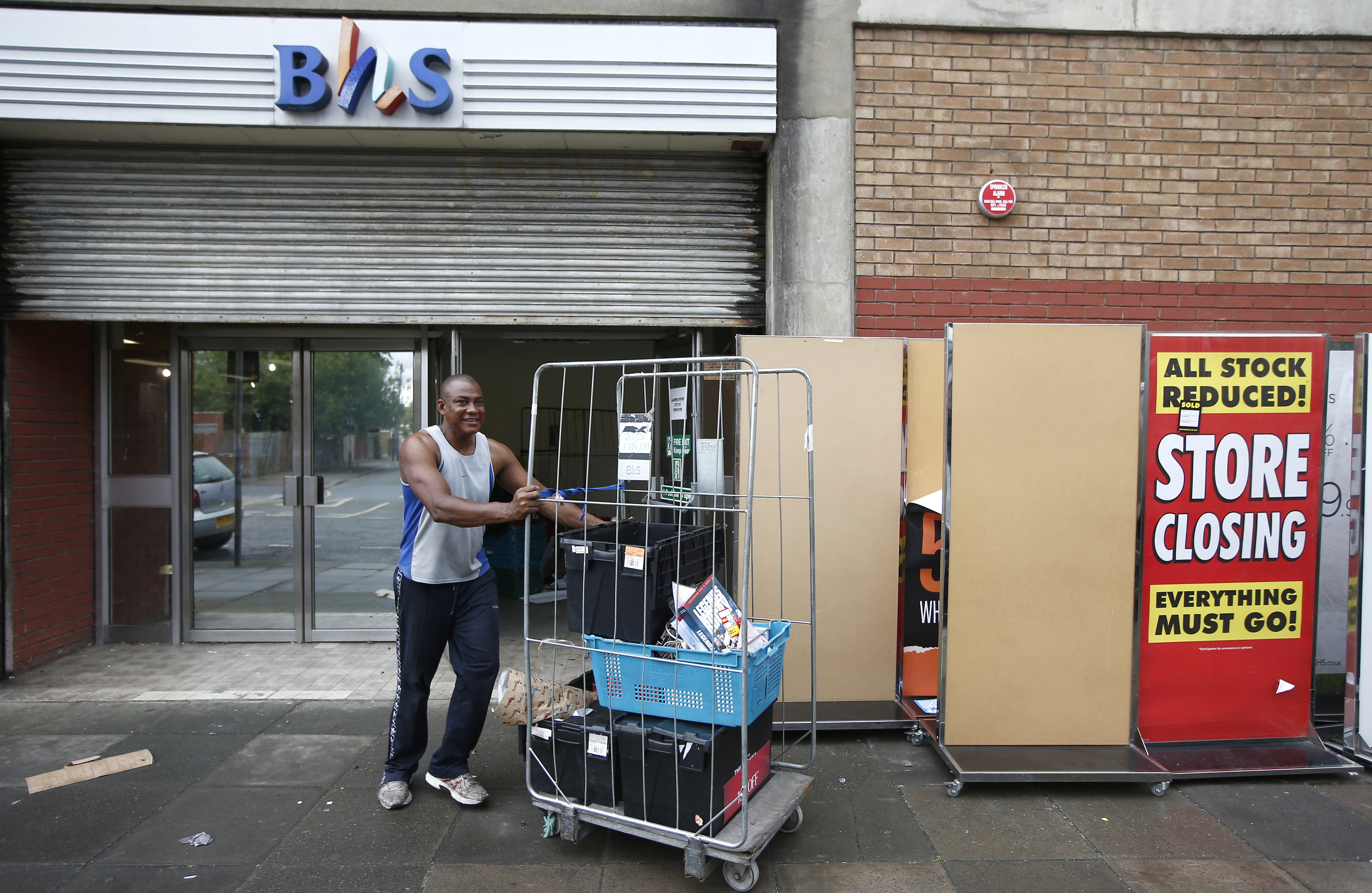 A worker removes items a BHS store. PwC received a record fine for its audits of the failed retailer