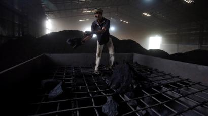 A labourer works inside a coal yard on the outskirts of Ahmedabad, India.