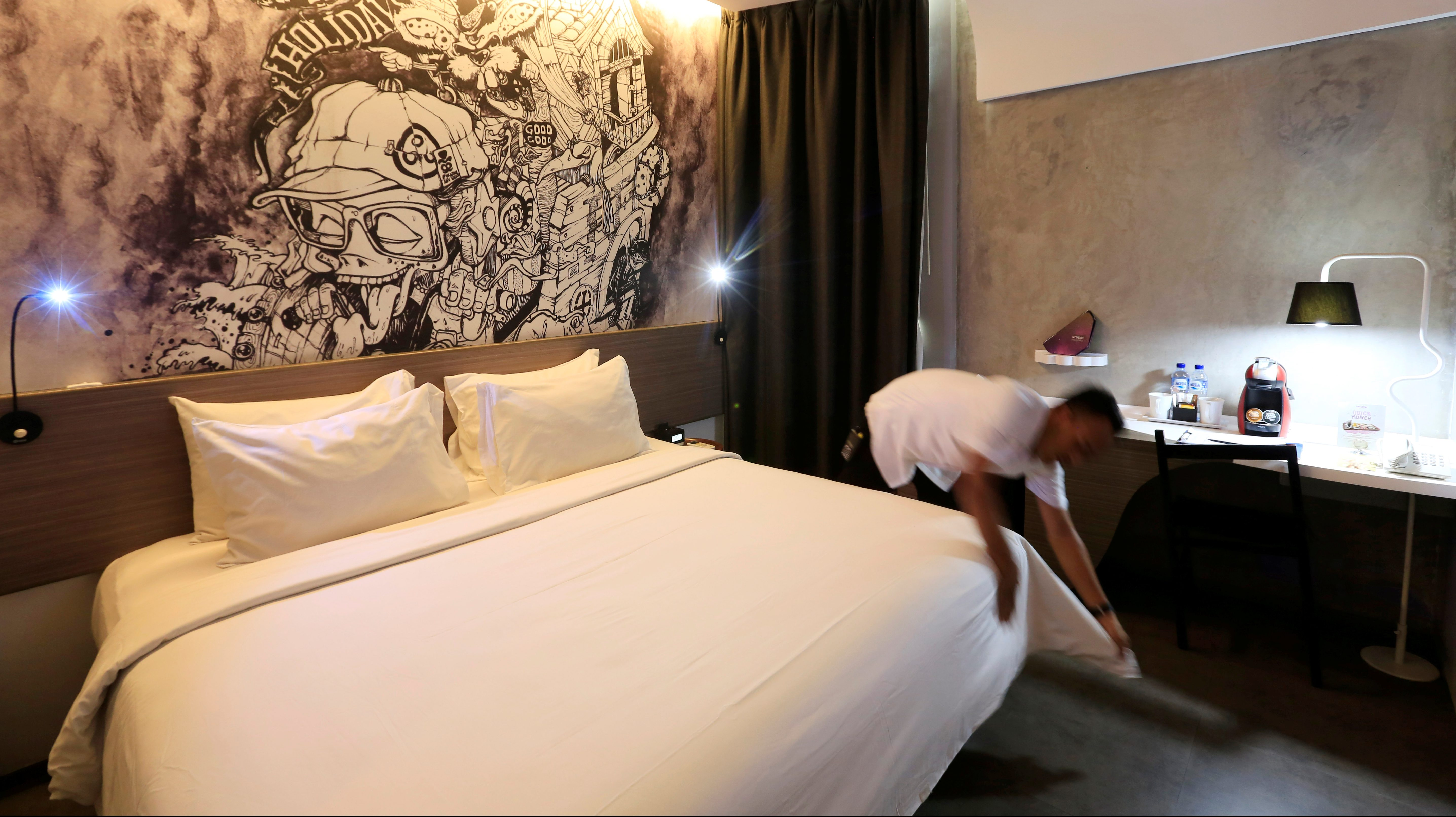 A worker prepares a bed, at a room of the Artotel, next to a painting by Indonesian artist Oky Rey Montha, in Jakarta