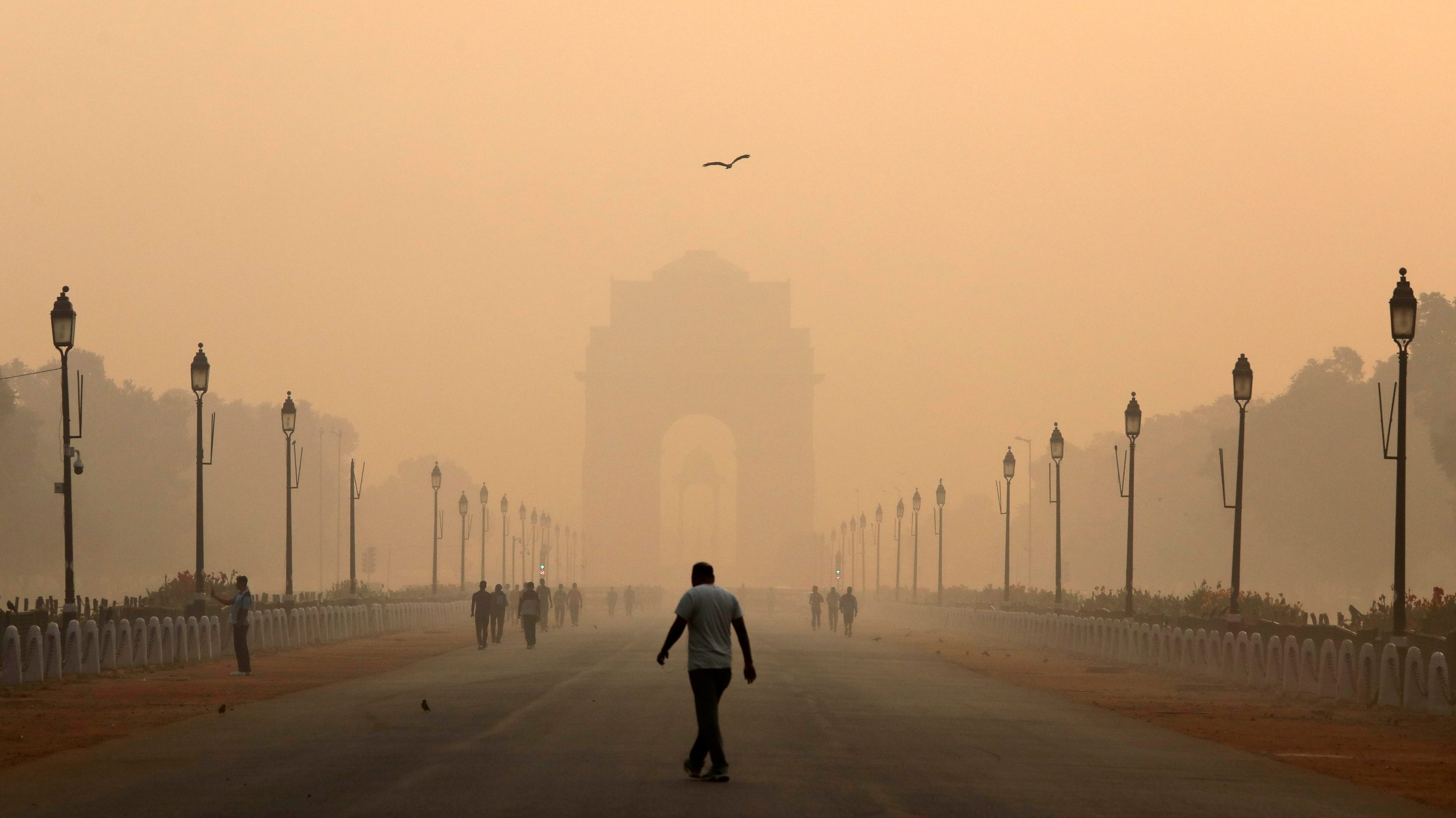 A man walks in front of the India Gate shrouded in smog in New Delhi