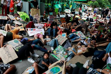 Environmental activist play dead as they participate in a Global Climate Strike near the Ministry of Natural Resources and Environment office in Bangkok
