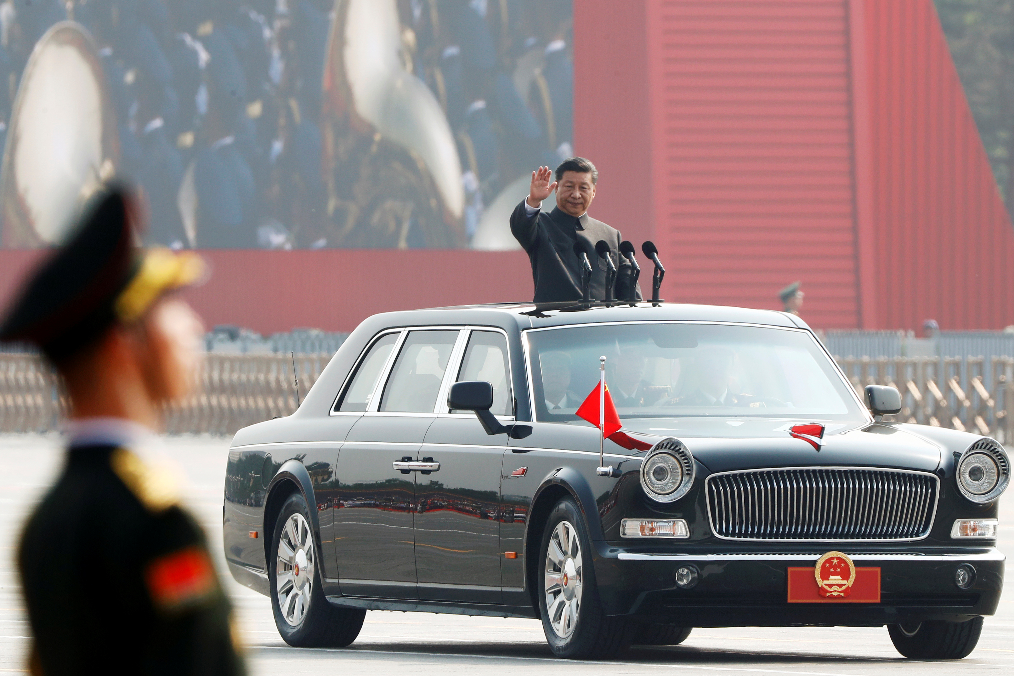 Chinese president Xi Jinping waves from a vehicle as he reviews the troops at the parade marking the 70th founding anniversary of the People's Republic of China in Beijing, China October 1, 2019.
