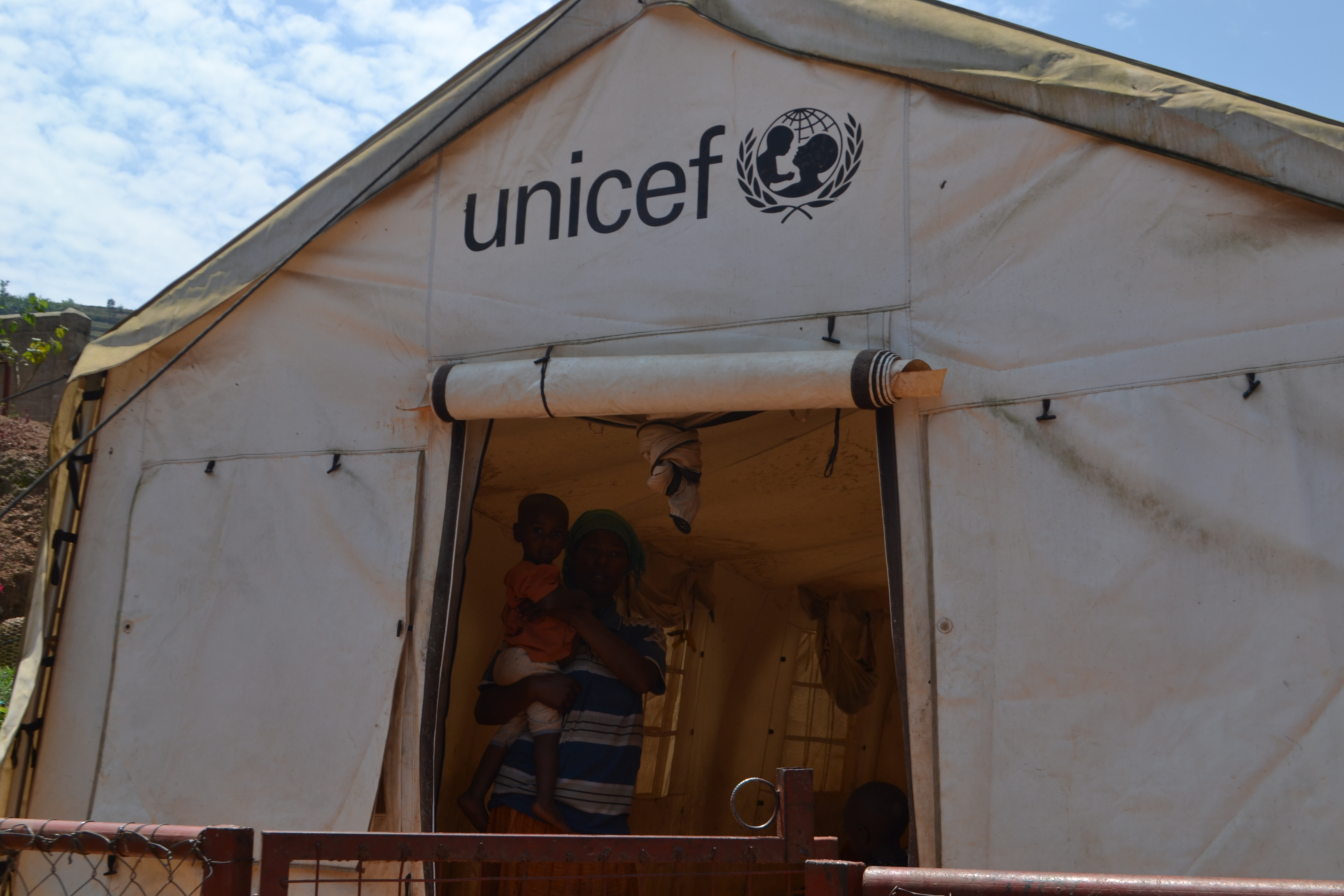 A mother and her child stand inside a UNICEF childcare tent at Sorwathe Tea Factory in Rwanda.