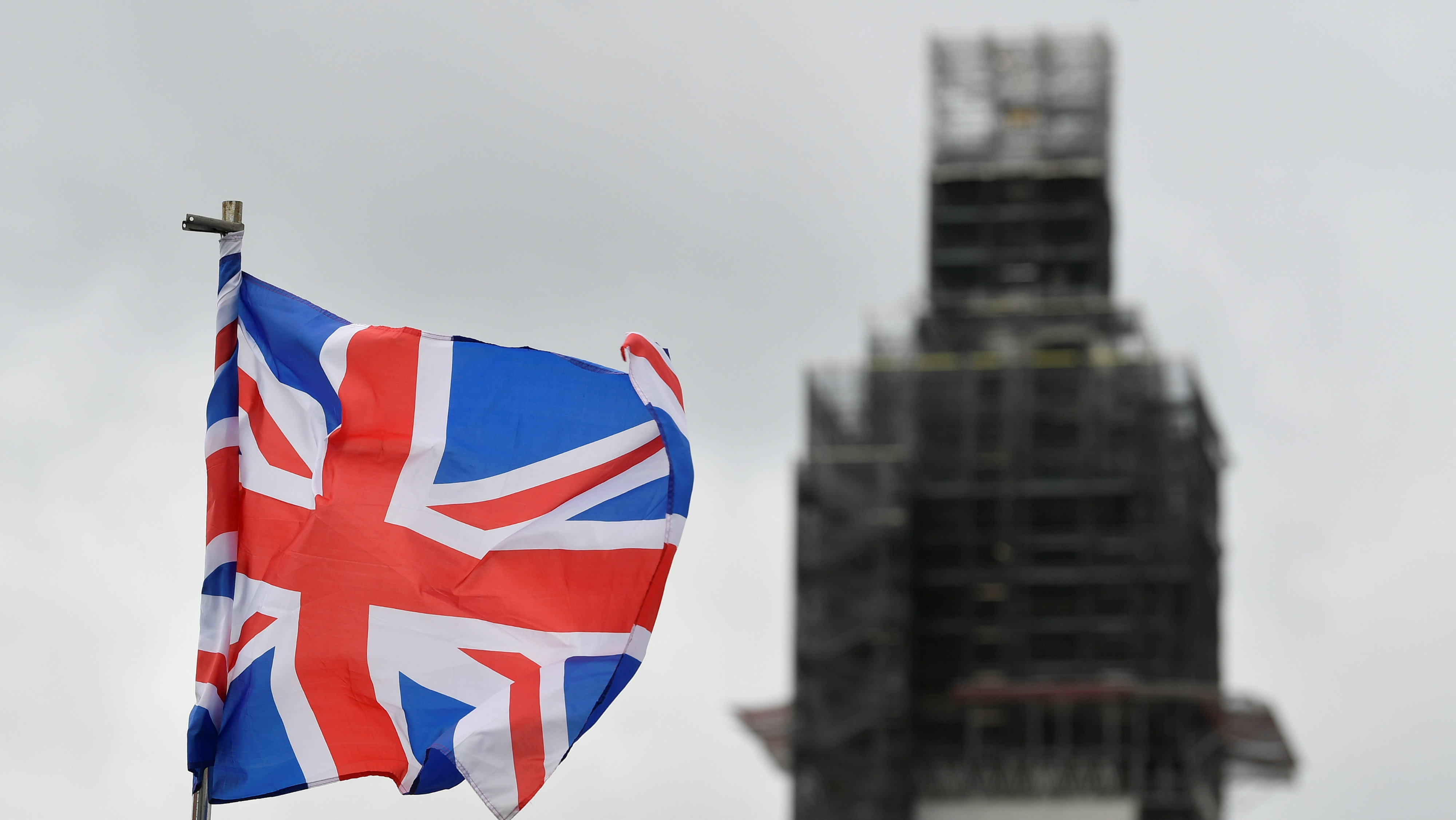 The British flag flutters in the wind near parliament