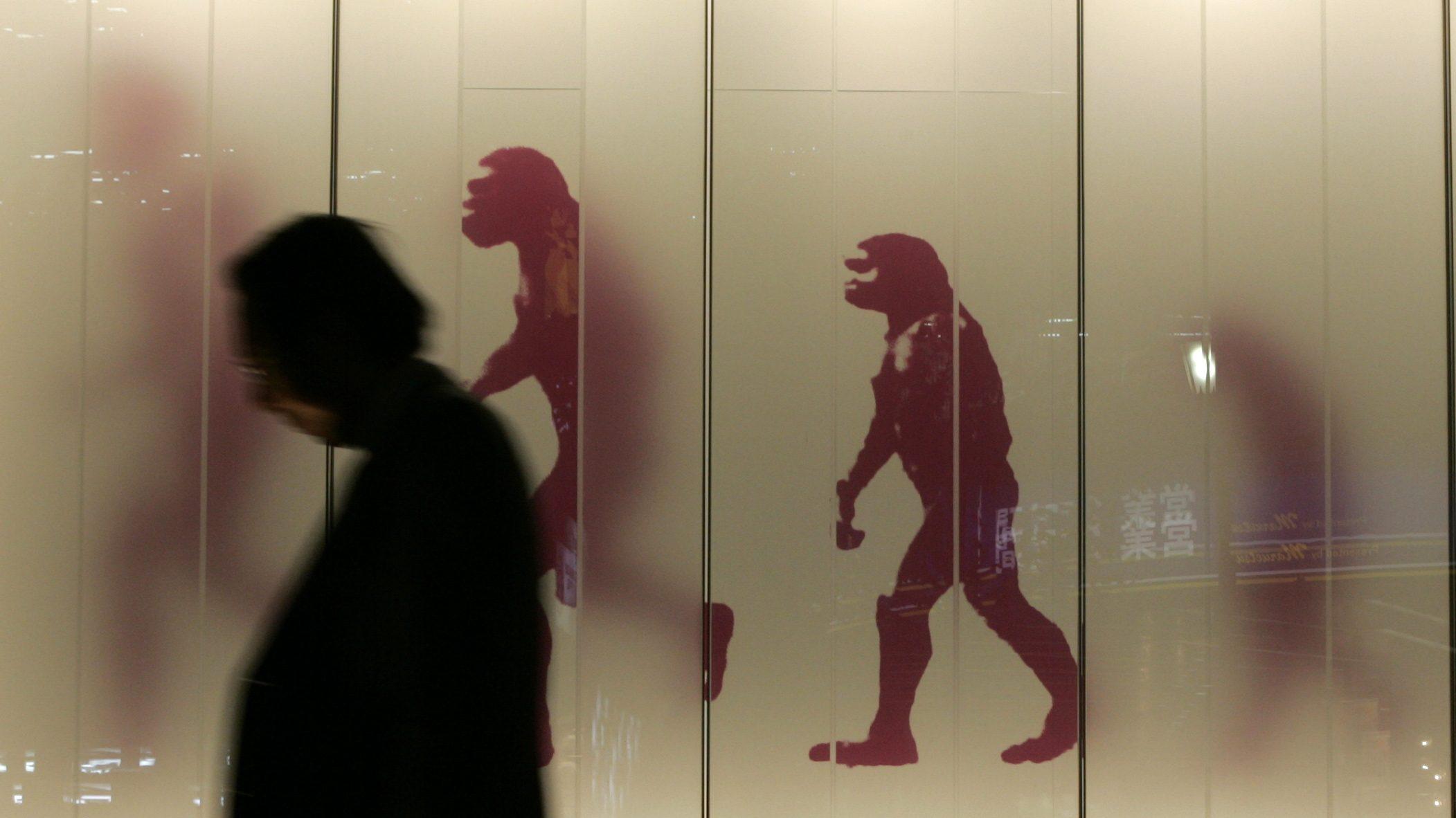 Man walking past evolution sign