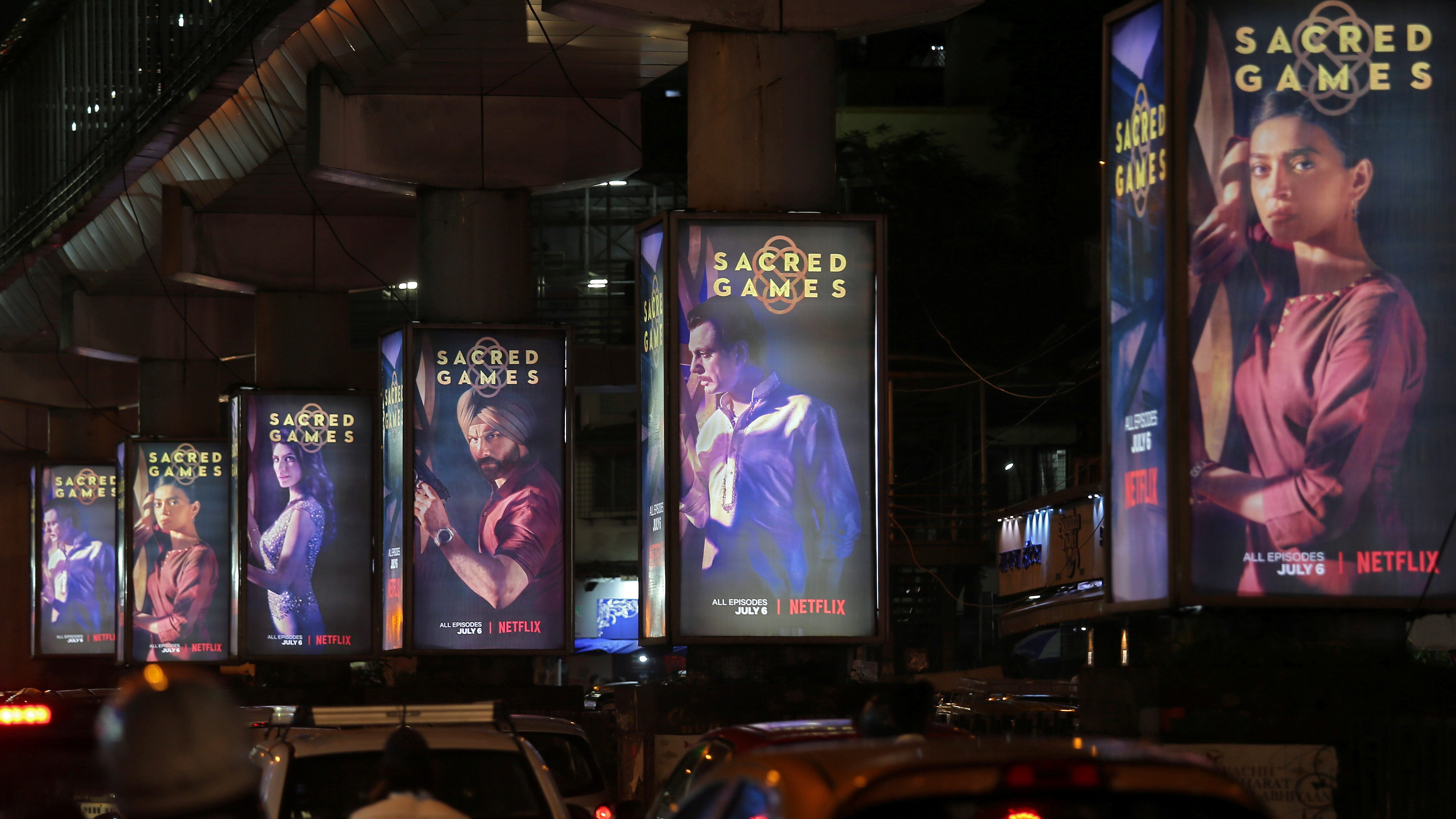 "Traffic moves on a road past hoardings of Netflix's new television series ""Sacred Games"" in Mumbai, India"