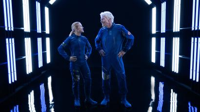 A woman and Richard Branson modeling the space suits
