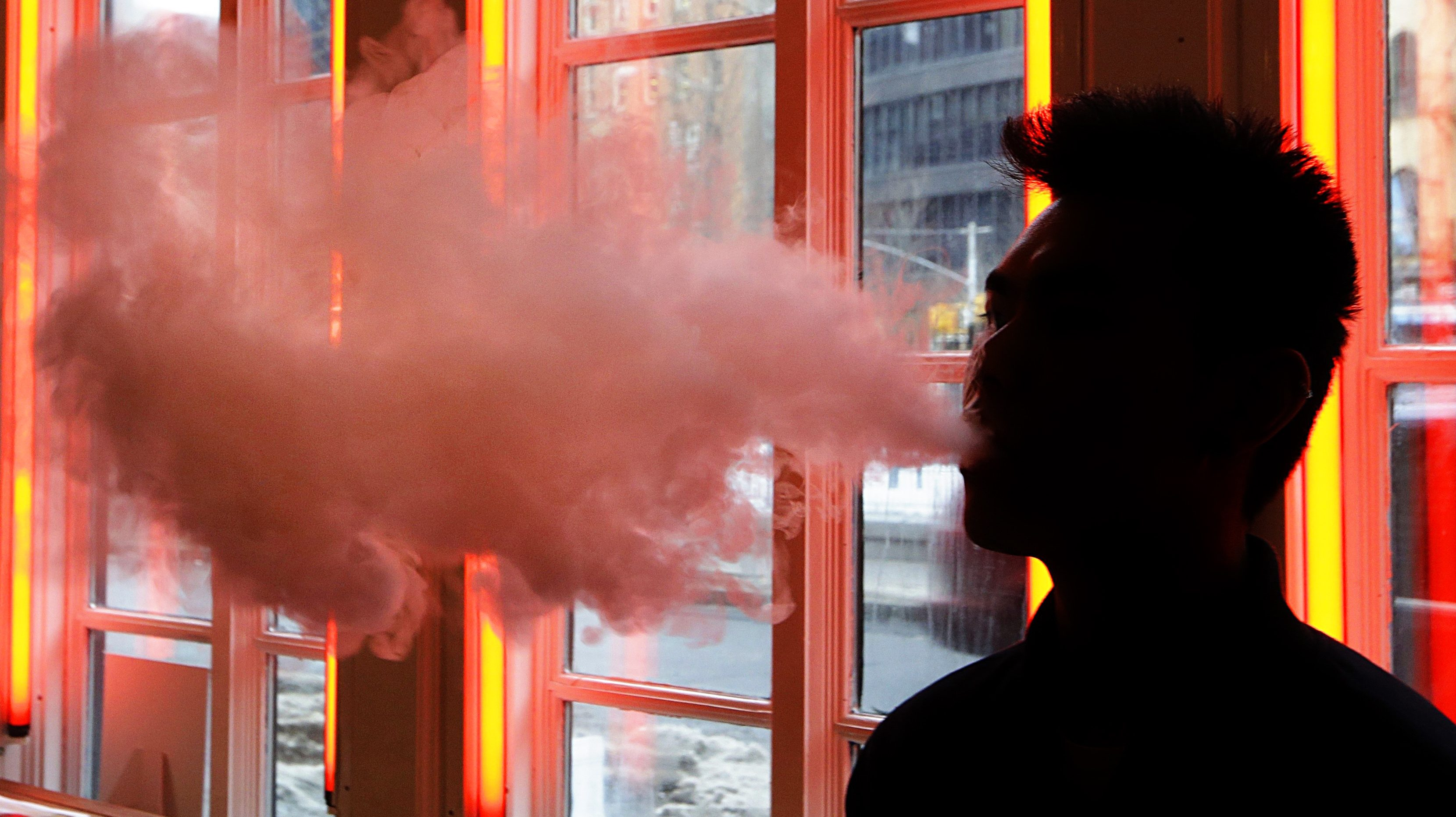 The silhouette of a person vaping.