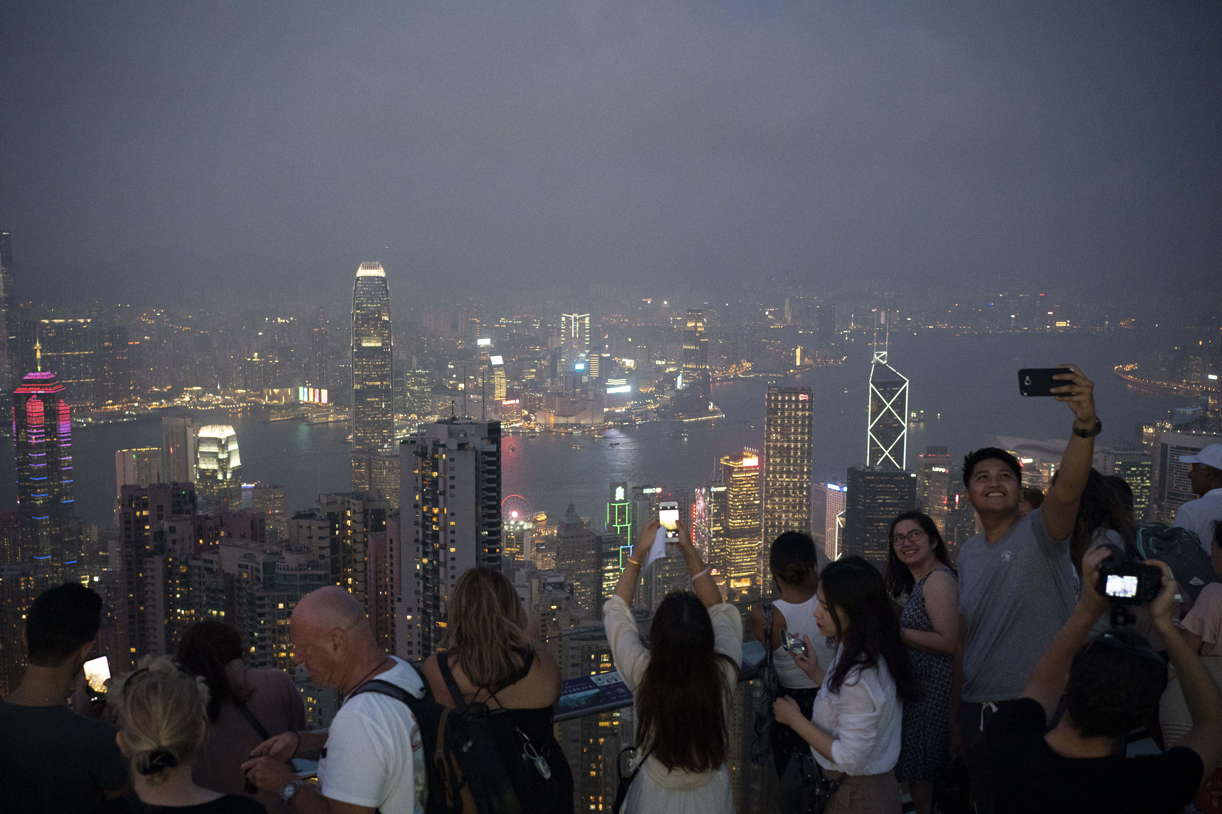 In this Oct. 9, 2019 photo, tourists take photos in a foggy evening at the Victoria Peak in Hong Kong.