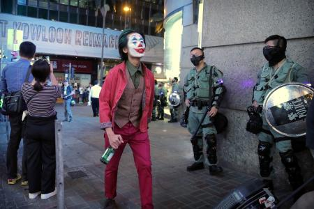 A man in a Halloween costume walks past police officers in riot gear in Hong Kong on Oct. 31.