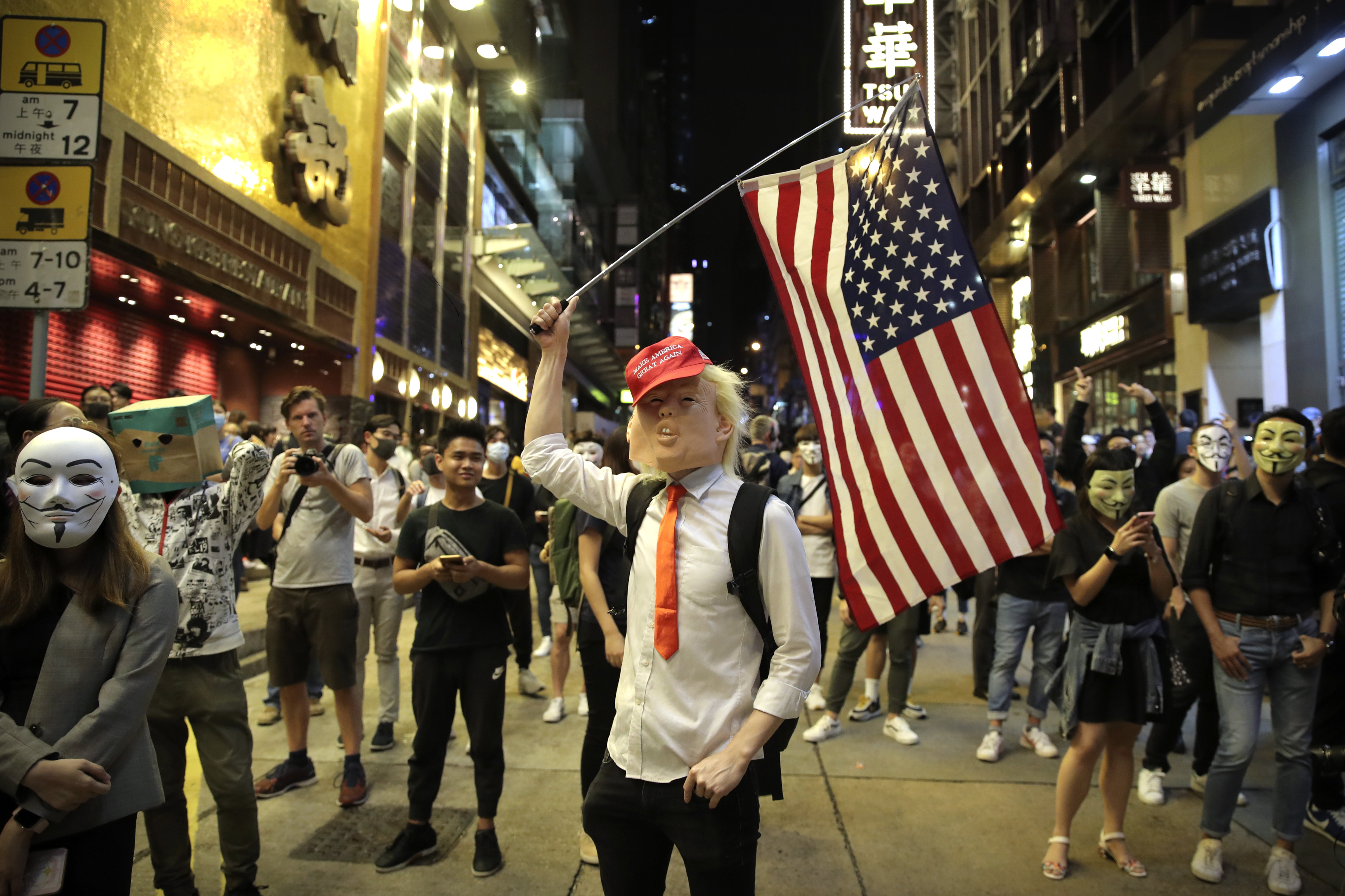 A person dressed as President Donald Trump waves an American flag as they stand on a street in Hong Kong on Oct. 31.