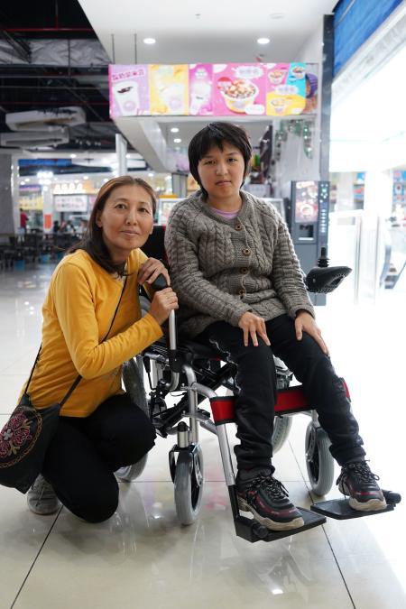 Aigul Orozbayeva and her daughter in the newly-bought electronic wheelchair came to Khorgos ICBC from Bishkek, Kyrgyzstan.